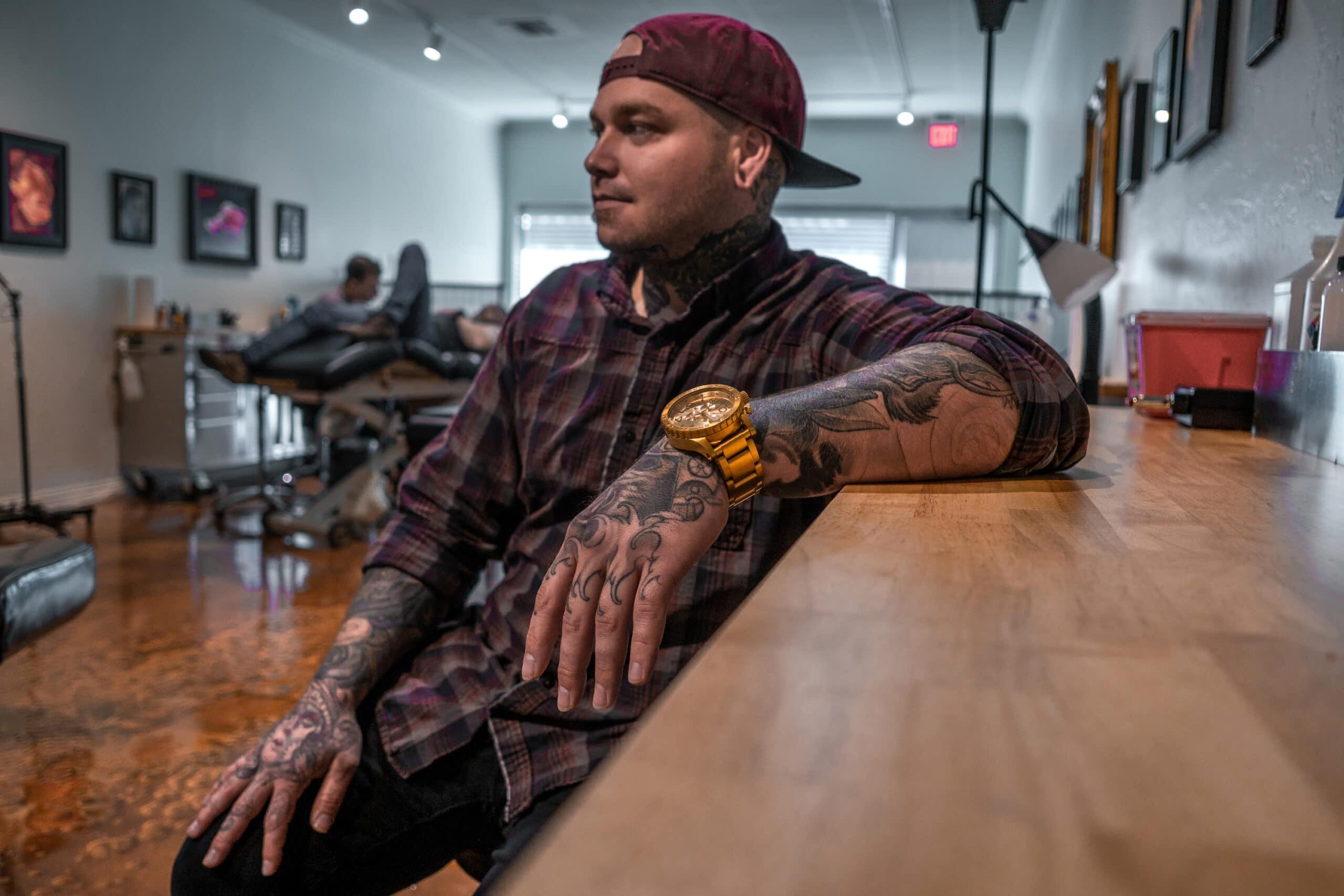Charles Taylor sitting at his tattoo station